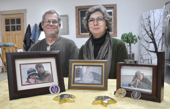 RICK AND NICOLE Lundin pose with photos of their son, Army Cpl. James Lundin, pictured below, who was killed in Iraq at age 20.