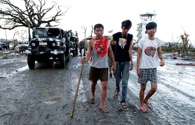 An injured man walks with an aid of a cane to get some treatment following a powerful typhoon that hit Tacloban city, in Leyte province in central Philippines Nov. 9. Rescuers in the central Philippines counted at least 100 people dead and many more injured Saturday, a day after Typhoon Haiyan , one of the most powerful typhoons on record, ripped through the region, wiping away buildings and leveling seaside homes with massive storm surges.