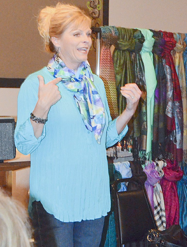 Doris Hess, owner of Wild Rags and Scarves, yesterday (Tuesday) shows women attending the monthly Lower Valley Christian Women's Connection luncheon how to tie scarves. Hess has a number of suggested knots to make everyday scarves look just a little different for any occasion.