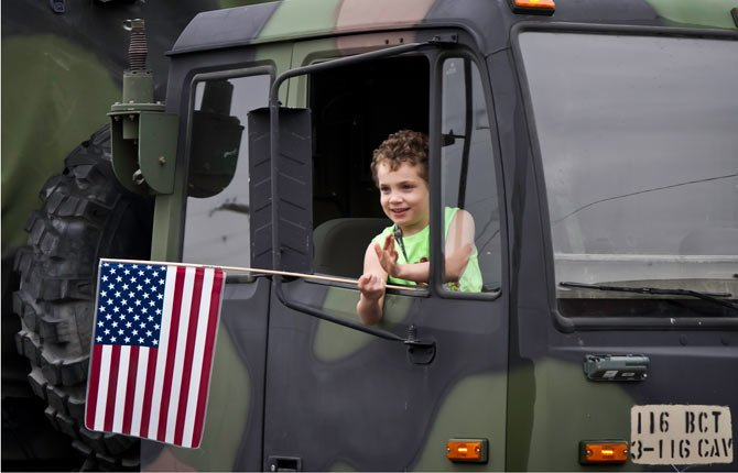 A young boy waves a flag from the window of a National Guard vehicle during the Veterans Day parade downtown The Dalles Monday.