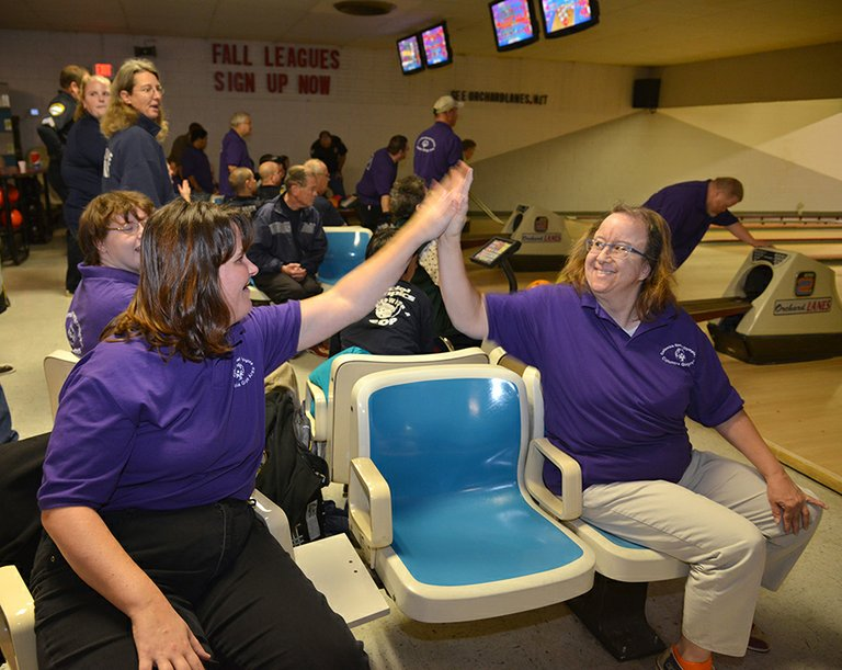 Hood River Special Olypmics' annual Bowling with the Cops and Firefighters fundrasier was a hit Monday evening at Orchard Lanes. The event brings together Special Olympics team members and local law enforcement and firefighters for an evening of friendly competition. Pictured are Rebecca Lund and Jani Gilbert giving high-fives after a great game.