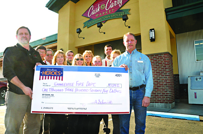 Cash and Carry Market owner Jim Schmidt (left) and several of his employees pass the big check to Danny Tackett, Grangeville Volunteer Fire Department (right) in the amount of $1,379.