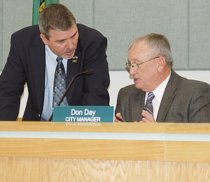 Mayor Jim Restucci (left) confers with Sunnyside City Manager Don Day before the city council meeting on Tuesday night.