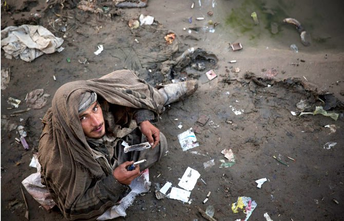 an Afghan drug addict smokes opium in a foul smelling river bed in the center of Kabul on Nov. 9. More than 1 million Afghans are addicts, living in squalor in its cities, sleeping on the street, in garbage-filled dried river beds reeking of human waste.