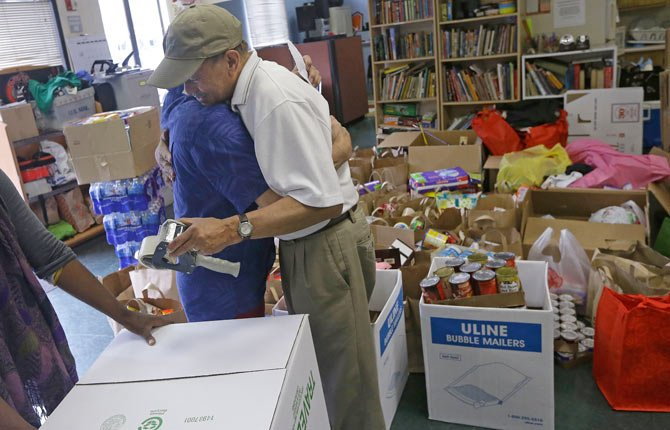 Rudy Asercion, executive director of the West Bay Pilipino Multi-Service center in San Francisco, right, hugs Arturo Marasigan, as he prepares boxes for donated items for victims of Typhoon Haiyan in the Philippines. The massive storm that hit the island nation Friday has affected at least 11 million people.