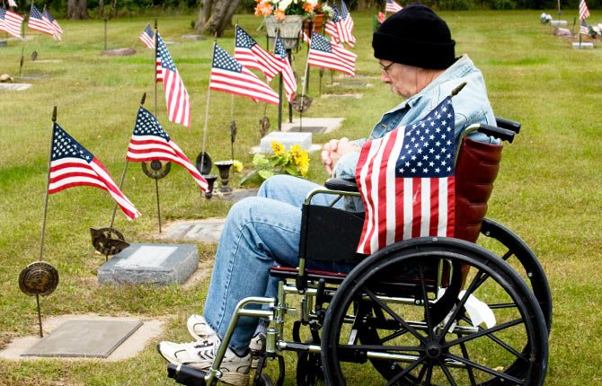 DISABLED VETERAN visits gravesite of lost comrade on Memorial Day. He and other veterans are often faced with long waits to get claims processed through the U.S. Department of Veterans Affairs, a situation the Obama Administration has asked attorneys across the nation to help alleviate.