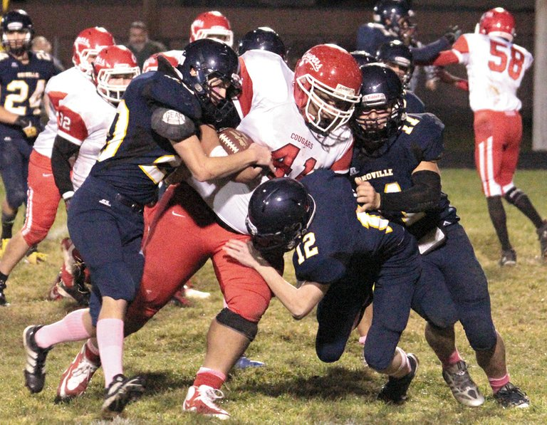 Oroville's Connelly Quick, Ricky Mathis and Luke Kindred strain to bring down White Swan's Tony Picard during Oct. 25 game.