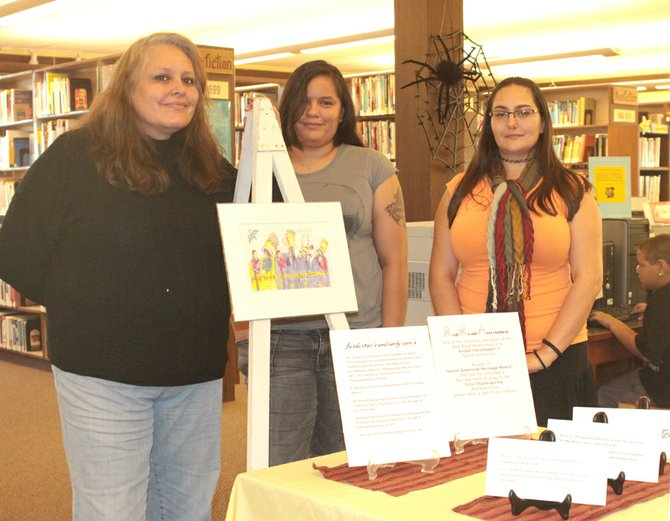 Cheryl Grunlose, from left, and Kaylynn Grunlose, with the Red Road Association, and Sterlene Sena, from the Omak Library, pose with the exhibit about the first Thanksgiving.