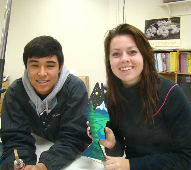 Fabian Rodriguez, left, and Lily Ade show a wooden salmon ornament they created for the Capitol Christmas Tree.