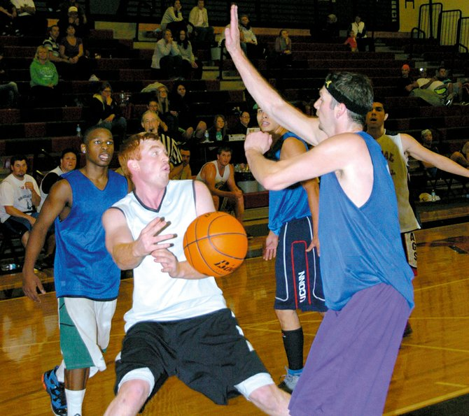David Pendergraft of the Knee Braces passes around Gabe Aubertin of Get Buckets in a championship game.