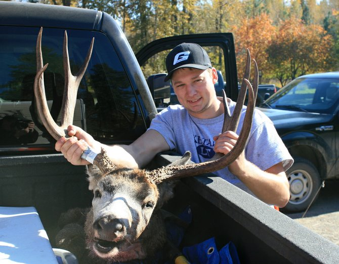 Colby Peterson, 22, shows off his prized 4x4 buck with a 27-inch antler-span on Sunday in Winthrop. The Marysville resident got a deer in his first attempt at hunting.