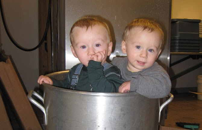 SHANE FUS, left and his twin brother Shawn found a new toy last year in the kitchen at Columbia Gorge Community College where mom, Rosa Fus, and her helpers prepare the annual feast sponsored by the Salvation Army branch in The Dalles. The now 2-year-old twins will visit the kitchen again for a short time in 2013 before being babysat in another location so volunteers can concentrate on their work.	Contributed photo