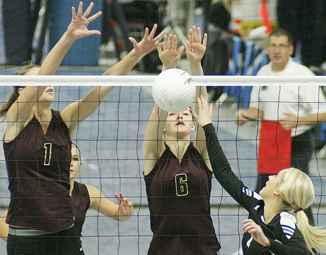 Sunnyside Christian's Brittany Broersma (#1) and Kate Newhouse (#6) attempt to stop an opponent from tipping the ball over the net.
