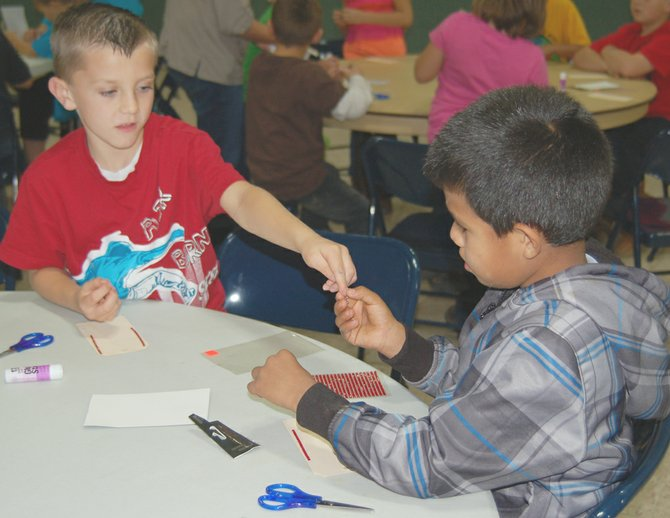 Elijah Wise (left) hands materials to Andres Reynaga as they work on a craft project together at a dinner and drama program for children. The group meets every second and fourth Wednesday of the month at the Sunnyside Presbyterian Church.