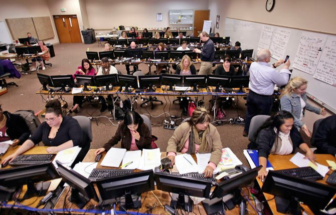 A roomful of people work to process applications for Cover Oregon, the states' health exchange program, in Keizer, Ore., Monday, Nov. 18, 2013. Despite grand ambitions, an early start, millions of dollars from the federal government and a tech-savvy population, Oregon's online enrollment system still isn't ready more than a month after it was supposed to go live. The state has resorted to hiring or reassigning 400 people to process insurance applications by hand.