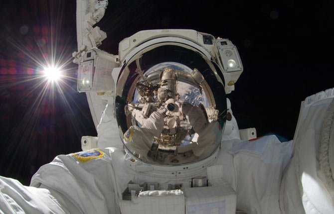 "Japan Aerospace Exploration Agency astronaut Aki Hoshide, Expedition 32 flight engineer, uses a digital still camera to expose a photo of his helmet visor during the mission's third session of extravehicular activity. ""Selfie"" the smartphone self-portrait has been declared word of the year for 2013 by Britain's Oxford University Press."