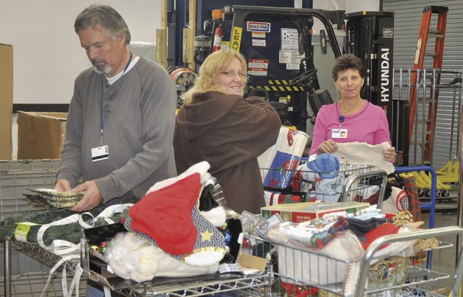 Val Jon Campbell, left, Tami Howell and Barbara Ingraham, all of The Dalles, work on sorting Christmas decor donated to the Goodwill store in The Dalles.