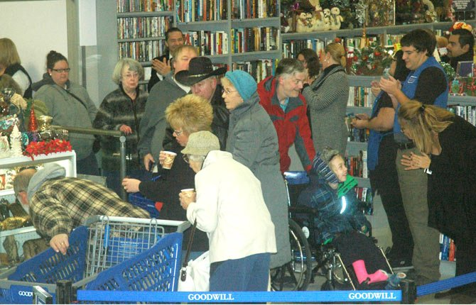 SHOPPERS CROWD through the entrance of the new Goodwill Store in The Dalles just after the 7 a.m. ribbon cutting. Regional Goodwill employees, right, applaud as the shoppers enter.