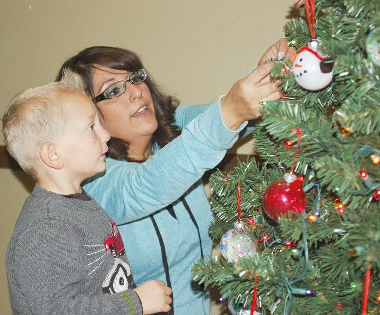 Four-year-old Blake Hauver lends a hand hanging ornaments on the Sunnyside United Methodist Pre-school Christmas tree under the watchful eye of his teacher, Audrey Brandsma. The tree, sponsored by the pre-school, will be placed at the Sunnyside Senior Center following tonight's annual Sunnyside Community Hospital Auxiliary Festival of Trees. The festival, being held at the Sunnyside Community Center, begins at 6 p.m. Tickets are available at the door.