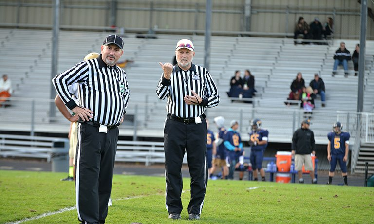 Wayne Smith (left) and Phil Hukari officiating a football game.