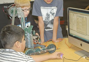 Young robot builders Vincent Martinez and Austin Bliesner (L-R) work to program their robot in preparation for the team's next competition. The Harrison Middle School seventh graders have already competed in two robotic contests, according to their advisor, Kari Bliesner.