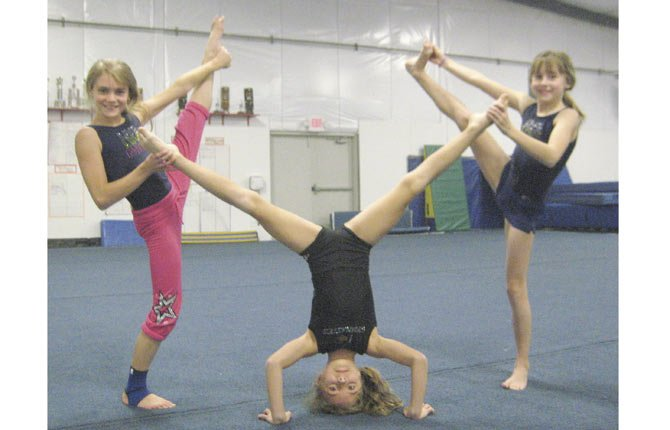 GYMNASTS Abby Beal, Gabby Haskins and Krissy Carter, from left, show off some moves after scoring first-place all-around finishes at the Northern Sectional on Saturday and Sunday. Riverside Gymnastics Academy took two team trophies at the meet on its way to qualifying 27 athletes for state.