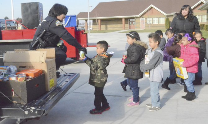 Students from the class of Angela Landrum (back right) collected the most food during a recent food drive at Sun Valley Elementary School. Here, they help load donations into the back of a Sunnyside Police Department vehicle. Collecting the donations this past Monday is Sunnyside Police Officer Melissa Rodriguez. The food drive assists Oasis Community Church's Underground outreach program and the Sunnyside Ministerial Association food bank. The kindergarteners at Sun Valley Elementary School collected more than 1,175 cans of food overall.