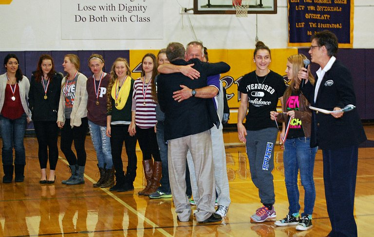 Pateros volleyball coach Gene Dowers receives a hug after his team, in the background, was presented the  Washington Interscholastic Activities Association Sportsmanship Award on Tuesday morning on the Nannies' home court.