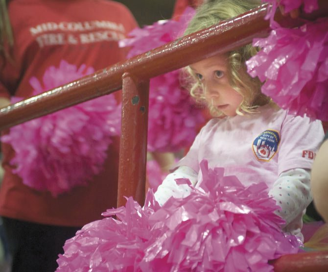 POMPOMS at the ready, Clara Wright, right, peeps under a railing to watch her dad compete for Mid-Columbia Fire and Rescue in Saturday's Shots and Ladders basketball game. The contest was held as a fundraiser for Special Olympics.