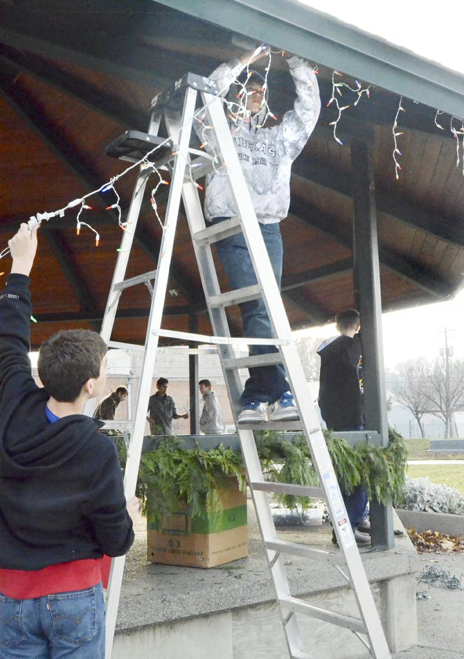 Recently, students from Sunnyside Christian High School, including (L-R) Chance Marsh and Cade Bosma, completed the decorations at Sunnyside's Centennial Square. Here, the two string lights on the pavilion as their classmates hang cedar boughs. The students maintain Centennial Square as a community service project.