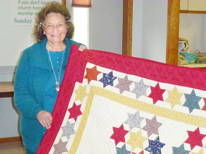 "Donna Gamble of Toppenish, seen here with her hand-quilted ""Seven Sisters"" quilt, is encouraging other quilters to support a quilt-making project for the Wounded Warriors project. Details will be provided to Horizon Quilters Unlimited of Yakima Valley at its club meeting Tuesday, Dec. 10, at 9 a.m., at Immanuel Lutheran Church Hall, 300 S. Euclid Road in Grandview. Special guest speaker will be Louise Bianchi, who is spearheading the Wounded Warrior program in Grandview. Project quilts will be supplied to wounded service personnel recuperating at Fort Lewis' Madigan Army Hospital in Tacoma. Gamble, who is a 20-year member of the quilting group, usually makes family quilts, but she has also made 230 quilts for wounded U.S. military personnel. ""This is a good project,"" she said."