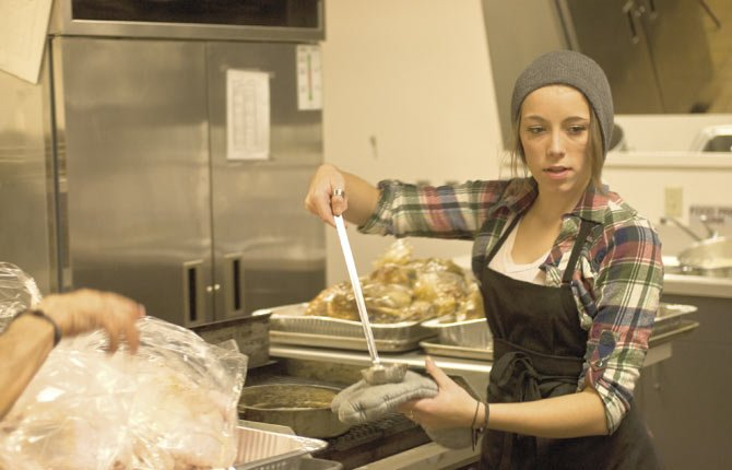 Shyanna Nails adds melted butter to  bagged turkeys  prior to loading them into ovens at the Columbia Gorge Community College's commercial kitchen in preparation for the Community Thanksgiving meal Thursday, starting at noon at St. Mary's Academy.