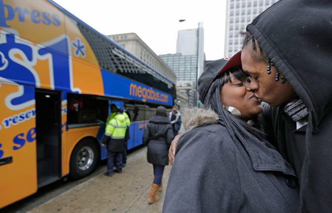 Shay Owens kisses her boyfriend Bryan Jordan in Chicago before boarding a Megabus for a trip to Atlanta Nov. 26. Millions of Americans are hurtling along the nation's jumble of transportation arteries for Thanksgiving, and more of them are discovering the bus.