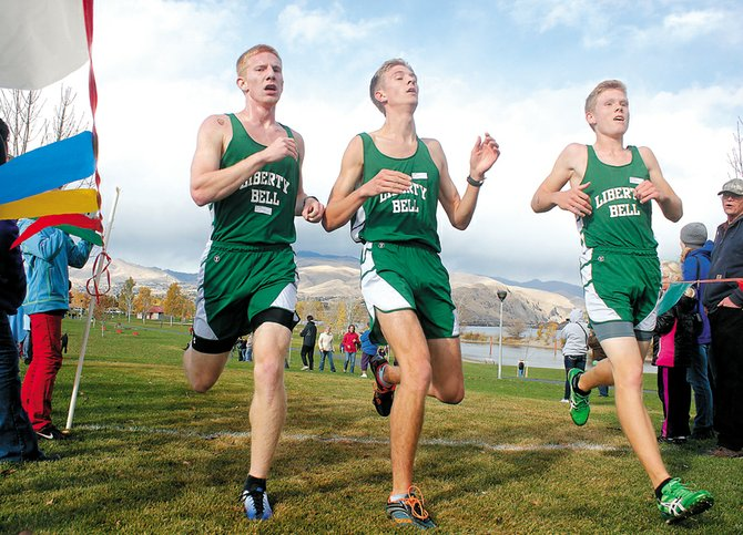 Liberty Bell High School runners, left to right, Willie Duguay, Liam Daily and Ben Klemmeck cross the finish line together, setting up a game of rock, paper, scissors to resolve the District 5-6 placing order Saturday at Walla Walla Point Park in Wenatchee.