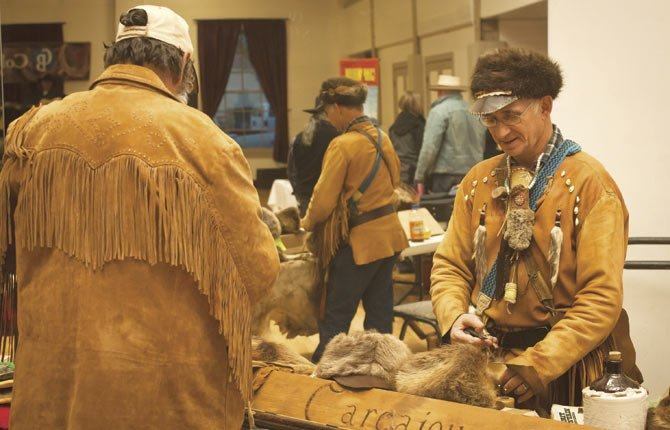 """Carcajou"" Cliff Elliott of Odell shows off some of his fur hats, shooting bags and other handmade products during the annual Cowboy Gathering in The Dalles Saturday, Nov. 30 at the Civic Auditorium. His work can also be seen online at Etsy.com."