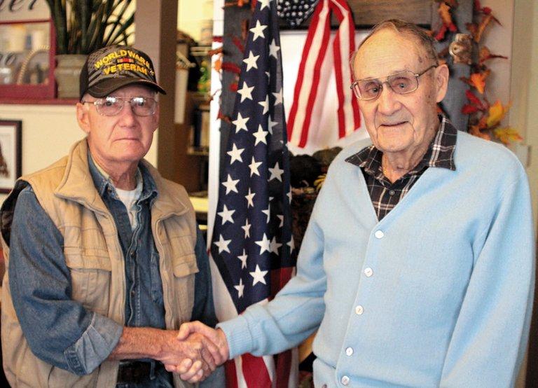 World War II veterans Vance Raimey, left, and Douglas Hull shake hands Saturday at the Corner Bistro in Omak.