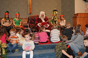 Santa Claus (Fred Smith of Grangeville) reads the Christmas story to children at the annual Breakfast and Pictures with Santa event set for the Grangeville Church of the Nazarene. This will be held Dec. 14 this year, 10 a.m. to noon.