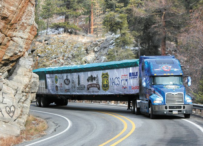 The tractor-trailer carrying the 88-foot Capitol Christmas Tree rounds hanging rock, on state Highway 20 east of Tonasket, as it makes its journey from the Colville National Forest to Washington, D.C.