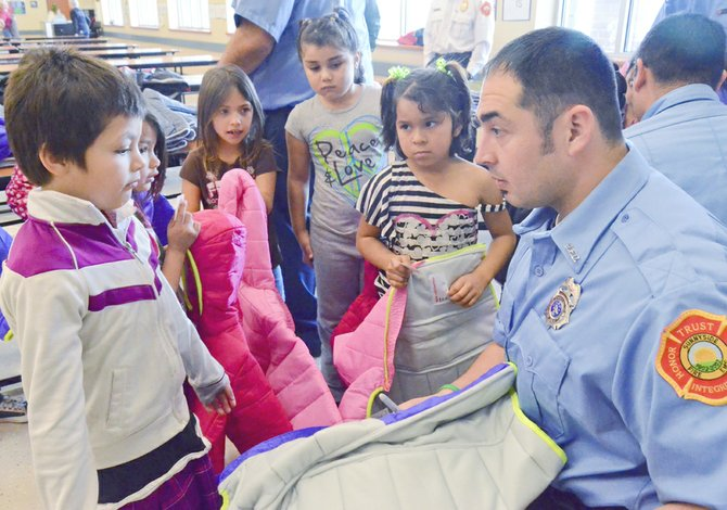 Kindergarten students at Sunnyside's Sun Valley Elementary School surround Sunnyside firefighter A.J. Barrera this past Tuesday as firefighters hand out coats as part of Operation Warm. The Sunnyside Professional Firefighters Association and Sunnyside Fire Department participated in the coat giveaway organized by the International Association of Firefighters, providing coats to children in need. More than 25 kindergarten students locally received a new coat as a result of the effort.
