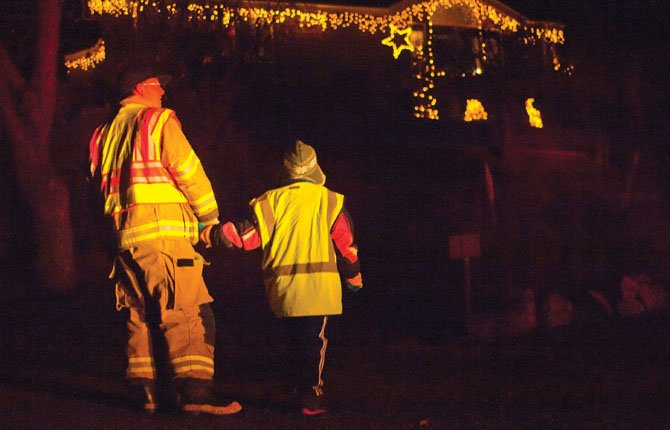 Dallesport firefighter Jason Peery and his daughter Alissa admire some Christmas lights Dec. 3 on the east side of The Dalles as they shepherd a group collecting donations for the ELFF (Everybody Loves a Fire Fighter) food drive Tuesday' night. 	Mark B. Gibson photo
