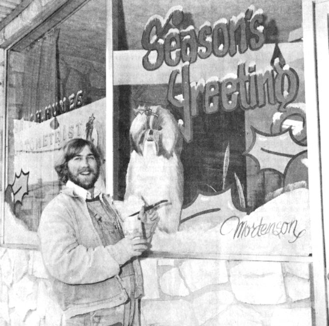 1973: Jolly old sign painter Bob Mortenson kept busy brightening up Sunnyside storefronts with decorative Christmas motifs. Here, he is decorating the window for Dr. Humes, using the doctor's dogs as inspiration.