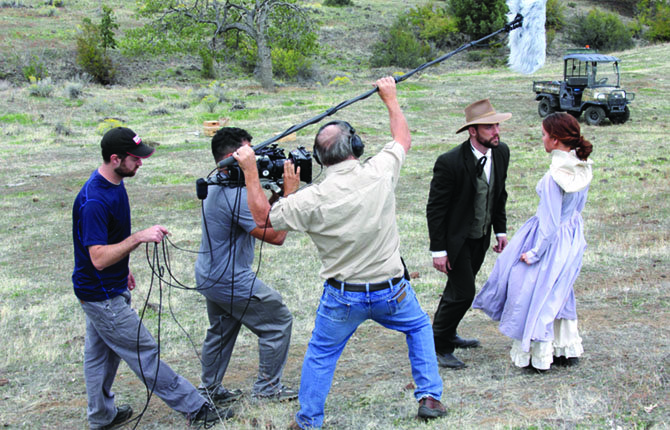 "A FILM CREW shoots a scene from a cinematic trailer for ""The Mystery of Bonney's Canyon,"" a novel by Mike Davis, starring actors Michael Draper and Paige McKinzie, at right. Davis will be on hand Saturday for the trailer's premier at the Columbia Gorge Discovery Center holiday open house.	Contributed photo/Kristin Zabawa"
