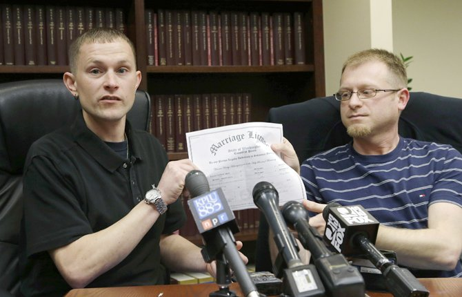 MICHAEL AND Eli Hall, right, hold their marriage license certificate, Tuesday, Dec. 3, 2013 as they talk to reporters in Seattle. Michael Hall, a locomotive engineer, is suing BNSF Railway, saying his husband Eli has repeatedly been denied health benefits even though gay marriage is legal in Washington state. 	AP Photo/Ted S. Warren