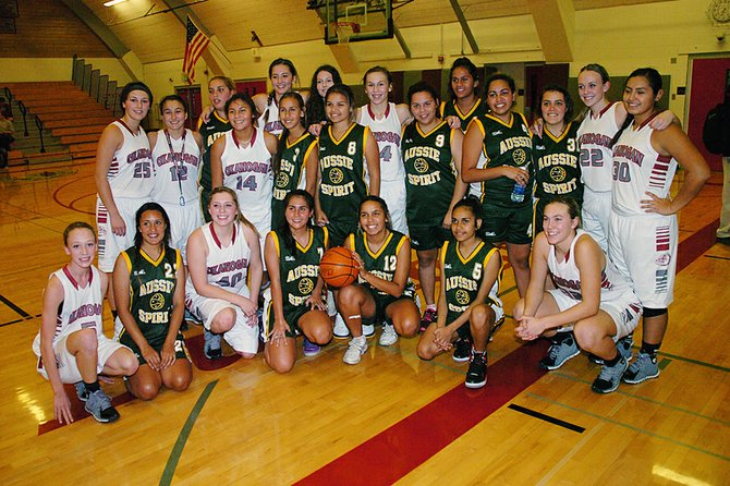 Okanogan High School girls and a select Australian basketball time pose for a photo together Wednesday night in the school gymnasium.