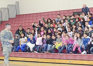 Army Specialist Dylan Johnston asks third grade students at Chief Kamiakin Elementary School about their goals.