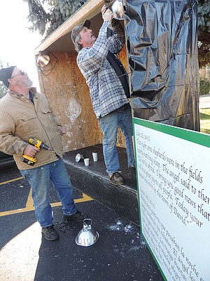 VOLUNTEERS Larry Clark, left, and Ron Smith in-stall lights in Drive-through Nativity booths, for this weekend's event at Church of the Nazarene, 22nd and Belmont.