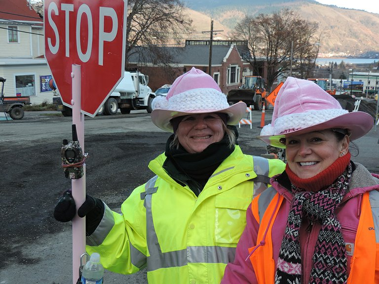 TOGETHER in the pink: Cheryl Rohan, left, and Betsy Keith model their seasonal stocking caps. Orange signs assist their work of keeping traffic moving safely through workzones.