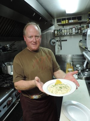 OWNER CHRIS LYNN puts the final touches on a plate of fettuccine.