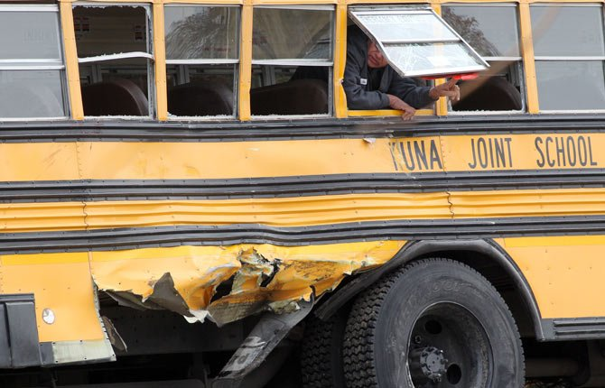 Law enforcement officials investigate the scene of a fatal crash on Thursday, Dec. 5 in Kuna, Idaho. Authorities say one child has died and five people were injured, including four children, when a dump truck collided with the school bus carrying elementary school students in Kuna, a town about 30 minutes from Boise.