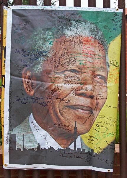 A giant signed poster with messages of support is attached to the former Soweto home, turned museum, of former South African president Nelson Mandela, Soweto, South Africa, today. Mandela died Dec. 5 after a long illness. He was 95. As word of Mandela's death spread, current and former presidents, athletes and entertainers, and people around the world spoke about the life and legacy of the former South African leader.